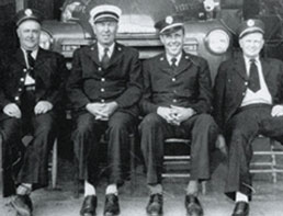 Fire Station crew members sit in front of a fire truck