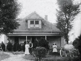 A couple and a young girl with a cow stand in the front yard of a house