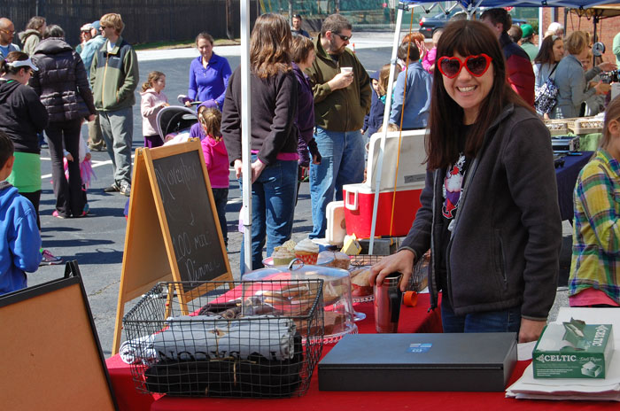A young woman in heart shaped sunglasses stands at vendor booth