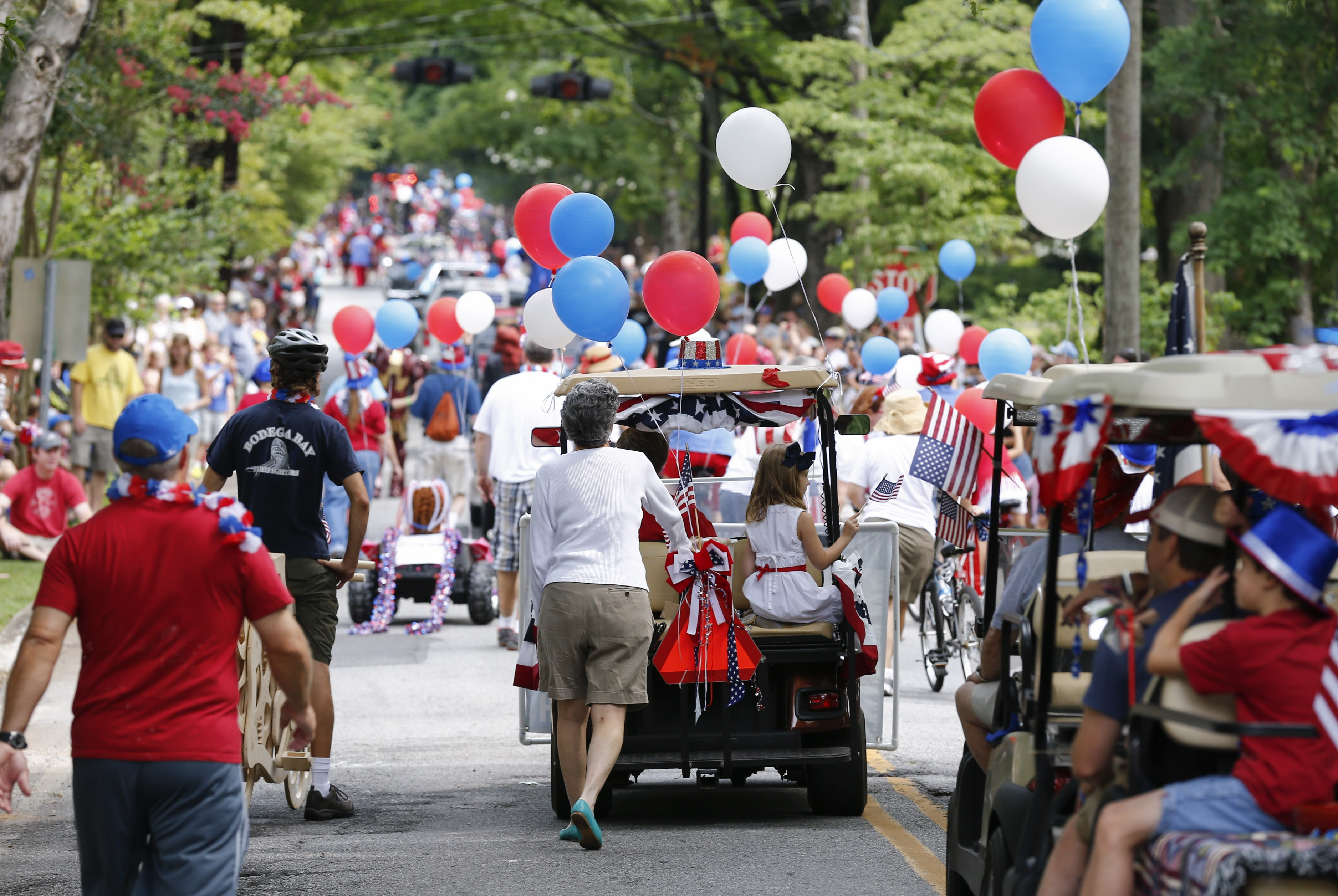 Residents walk down a busy street waving flags and holding balloons in a 4th of July Parade